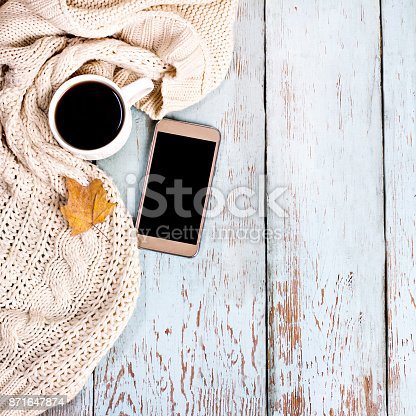 istock Autumn still life. Warm jersey, coffee, glasses, phone. 871647874
