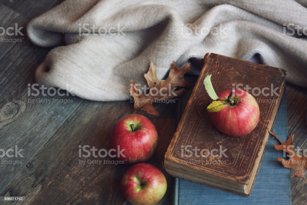 Autumn still life with apples, warm blanket, books and leaves over rustic wood background stock photo
