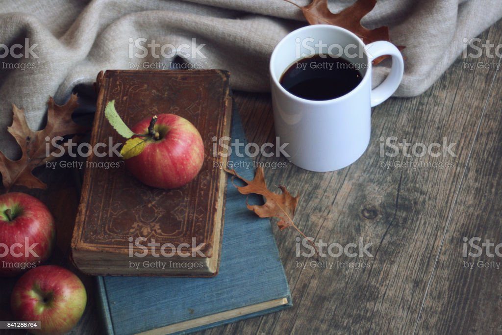 Autumn still life with apples, warm blanket, books, white coffee cup and leaves over rustic wood background stock photo