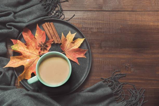 herbstliche stillleben mit tasse kaffee, lässt bunte trocken warmen schal auf holzbrett. kopieren sie raum. ansicht von oben. - wärmeplatte stock-fotos und bilder