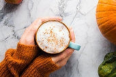 Autumn moody background with mug of latte coffee and pumpkins on marble table. Flat lay in fall colors. Female hands in cozy sweater