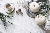 istock Autumn styled photo. Feminine Halloween desktop scene. Cup of coffee, eucalyptus, pine cones, white pumpkins and gypsophila flowers. Table background. Thanksgiving. Flat lay, top view. 1055990034