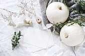 istock Autumn styled photo. Feminine wedding desktop stationery mockup scene with blank greeting card, eucalyptus, ribbons, white pumpkins and gypsophila flowers. Table background. Thanksgiving. Flat lay. 1049299126