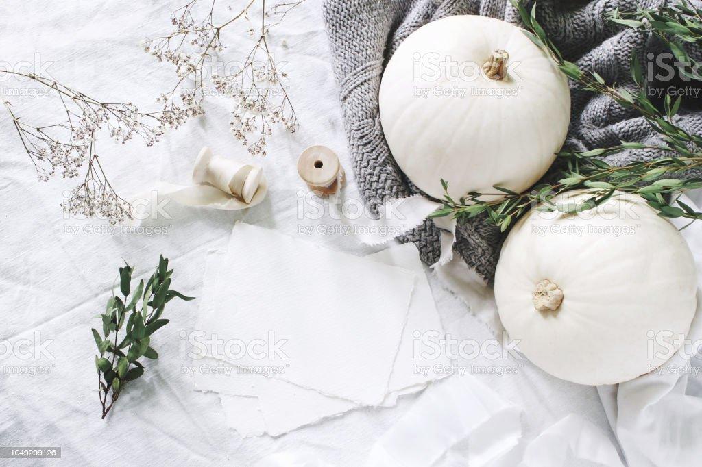 Autumn styled photo. Feminine wedding desktop stationery mockup scene with blank greeting card, eucalyptus, ribbons, white pumpkins and gypsophila flowers. Table background. Thanksgiving. Flat lay. stock photo