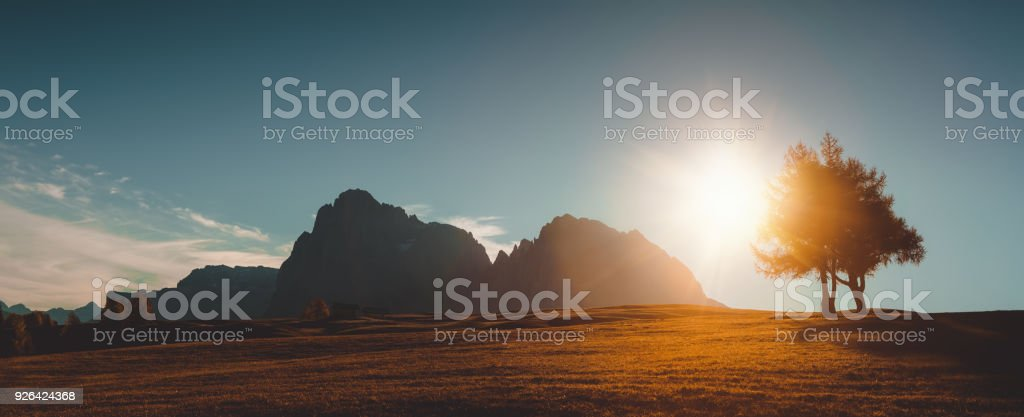 Autumn sunrise scenery with small alpine building and Odle - Geisler mountain group on background. Alpe di Siusi (Seiser Alm), Dolomite Alps, Italy. stock photo