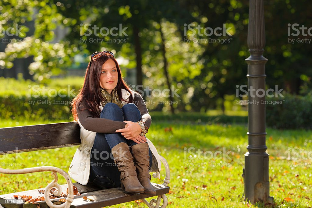 Autumn sunset park woman sitting on bench royalty-free stock photo
