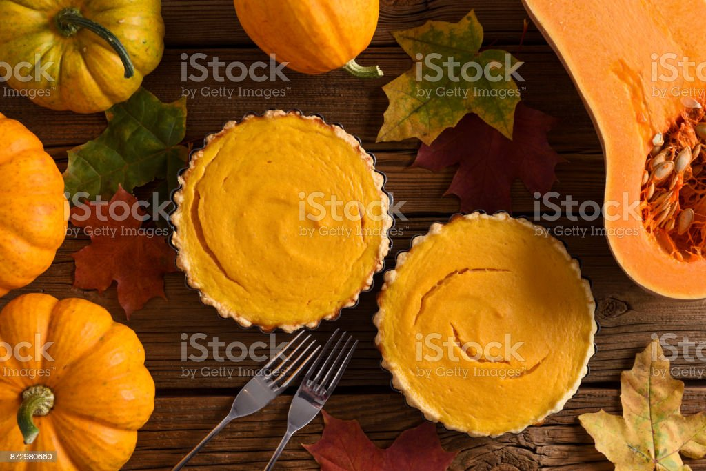 Autumn sweets flatlay. Couple of simple homemade pumpkin pies decorated with bright orange pumpkins, butternut squash and marple leaves stock photo