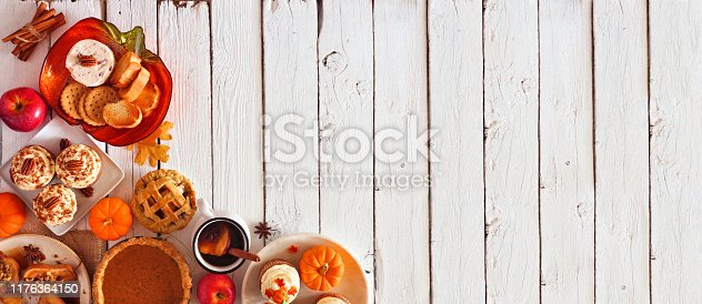 istock Autumn table scene corner border banner of pies, appetizers and desserts. Top view over a white wood background with copy space. 1176364150