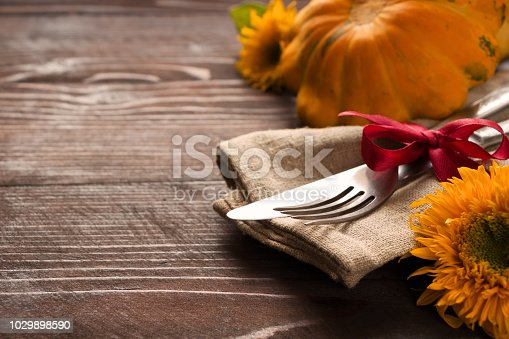 istock Autumn table setting.Fork and knife ,napkin, pumpkin and sunflowes on wooden table.Halloween or Thanksgiving day  background 1029898590