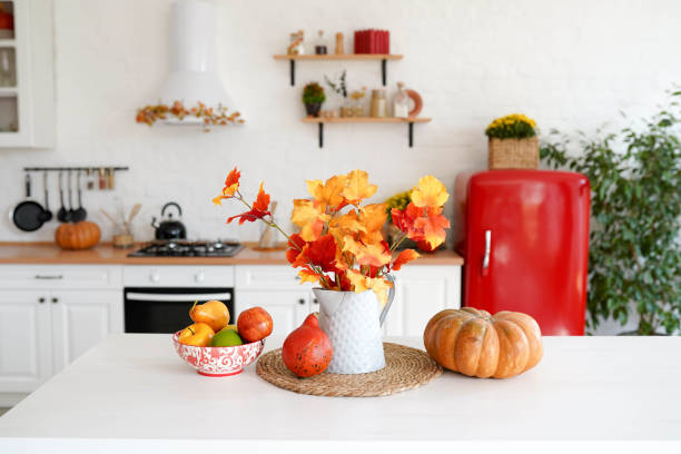 autumn table with vegetables in kitchen. red and yellow leaves in the vase and pumpkin on white background. autumn table with vegetables in kitchen. red and yellow leaves in the vase and pumpkin on white background. home decor stock pictures, royalty-free photos & images