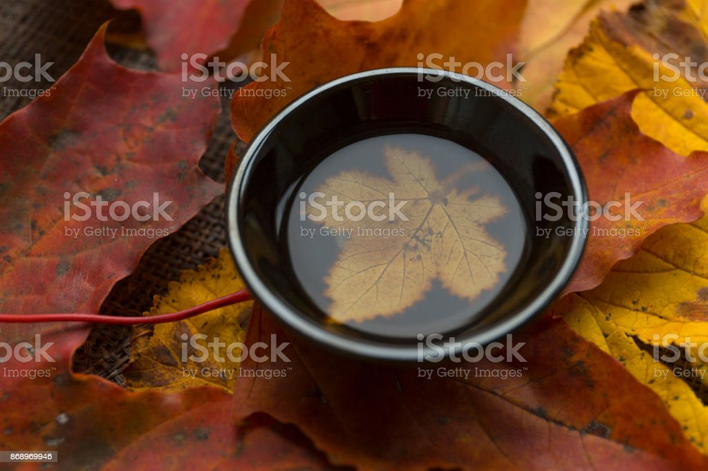 Autumn tea ceremony still life black cup of tea closup background stock photo