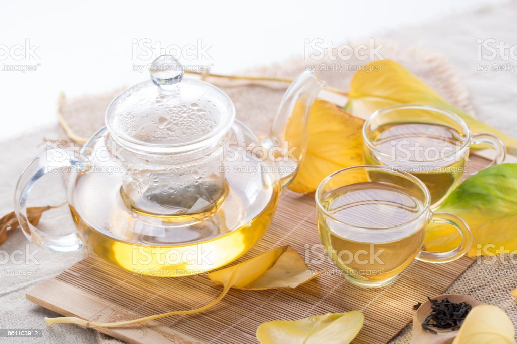 Autumn tea. Glass teapots and cups with autumn leaves on table. royalty-free stock photo