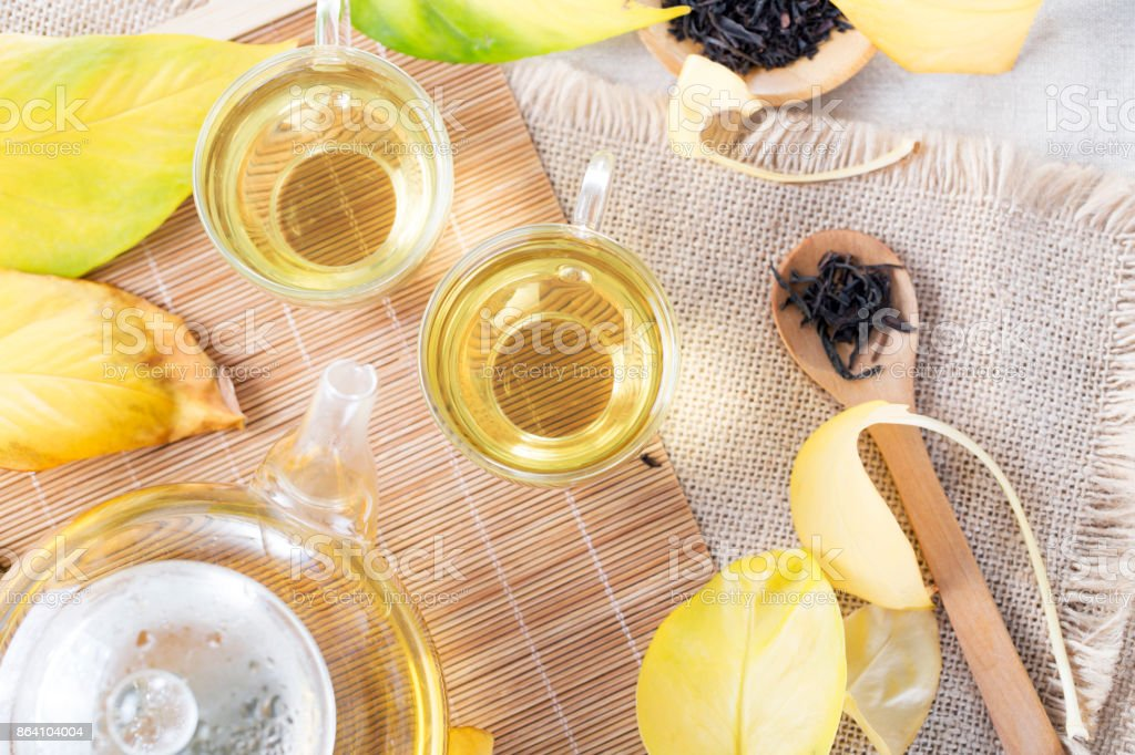 Autumn tea. Top view of glass teapot and cups with autumn leaves on table. royalty-free stock photo