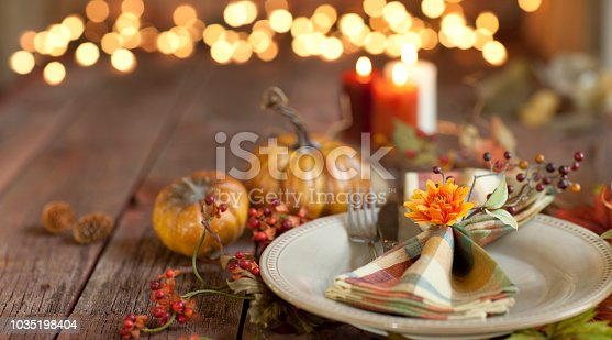 Autumn Thanksgiving dining table place setting on an old rustic wood table with candles and defocused Christmas lights