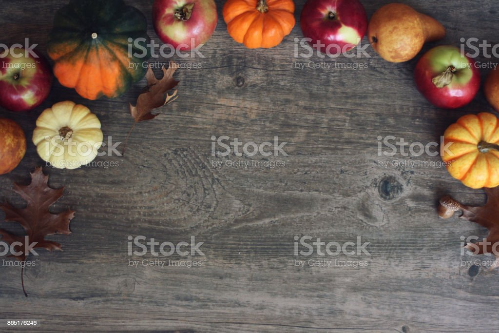 Autumn Thanksgiving Harvest Background with Apples, Pumpkins, Pears, Leaves, Acorn Squash and Nut Border Over Wood, Shot Directly Above stock photo