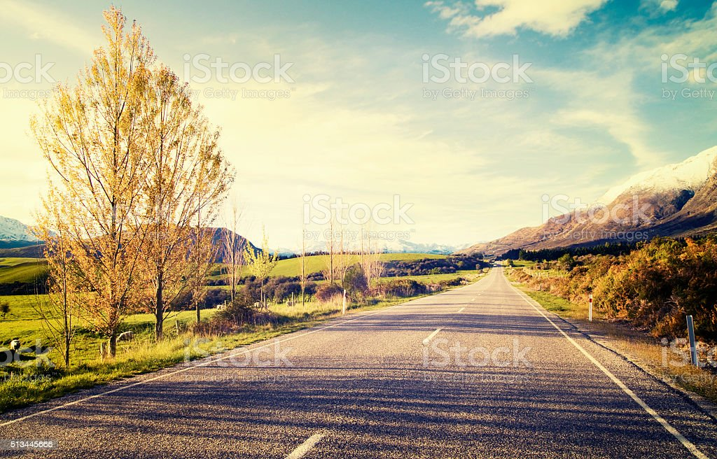 Autumn Themed Country Road With Mountain Range Concept stock photo