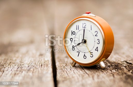 Autumn, time change, daylight savings concept - retro orange alarm clock