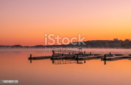 Peaceful lake view in Manasquan reservoir, New Jersey featuring mist on the background and beautiful sunrise colors