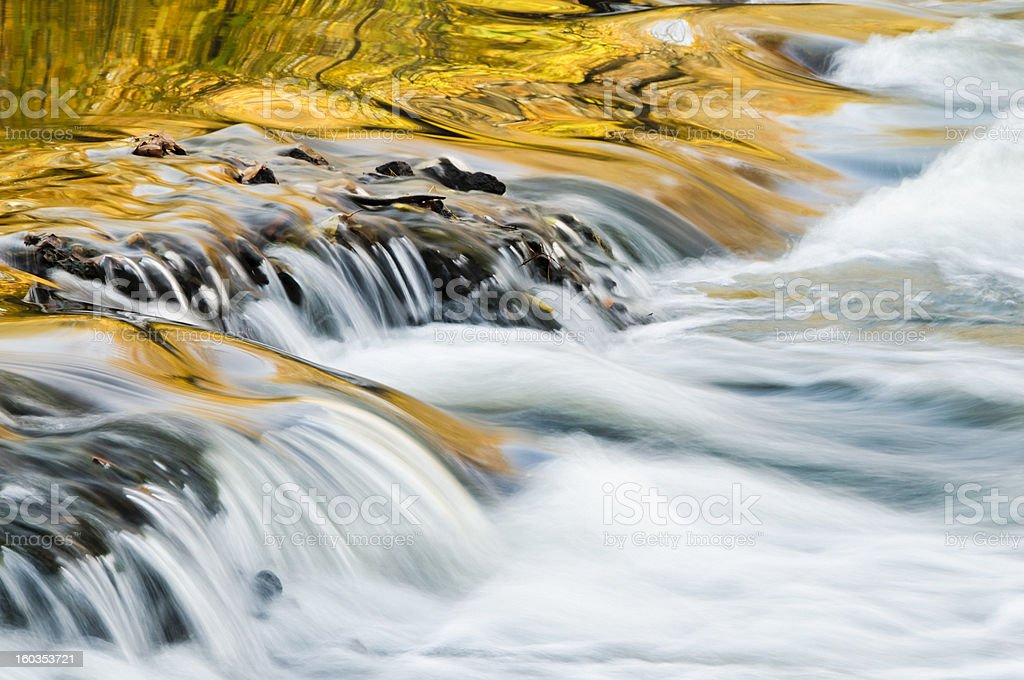 Autumn trees reflected in a cascading stream. royalty-free stock photo