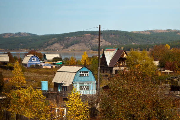 Autumn view of  brightly painted homes in village by river Autumn scene between Ulan Ude and Ust-Barguzin, Russia russian dacha stock pictures, royalty-free photos & images