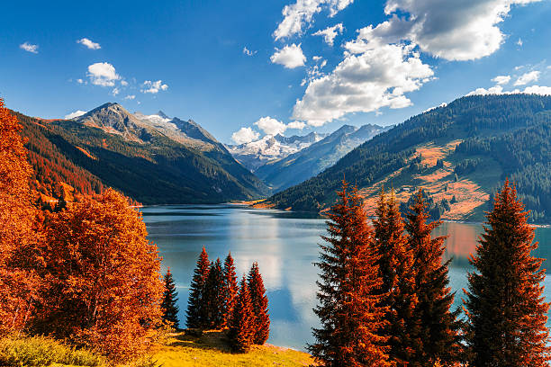 Autumn view with red foliage of Alps with lake stock photo