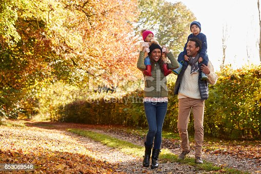 istock Autumn Walk With Parents Carrying Children On Shoulders 653069546