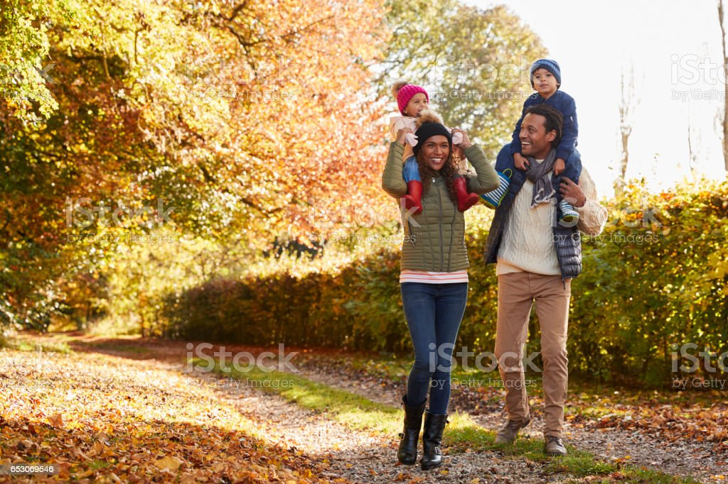 Autumn Walk With Parents Carrying Children On Shoulders stock photo