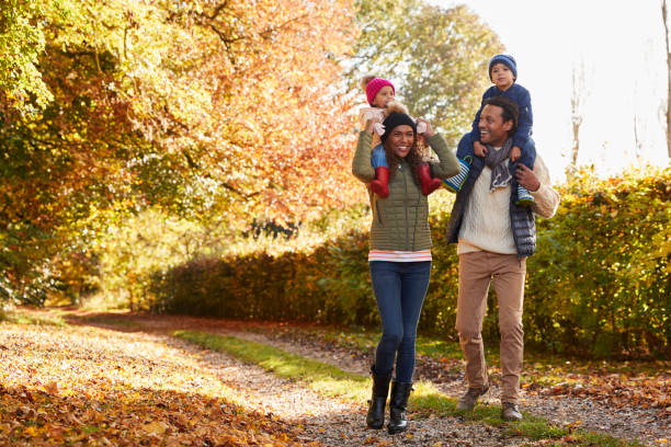 autumn walk with parents carrying children on shoulders - rural lifestyle stock photos and pictures