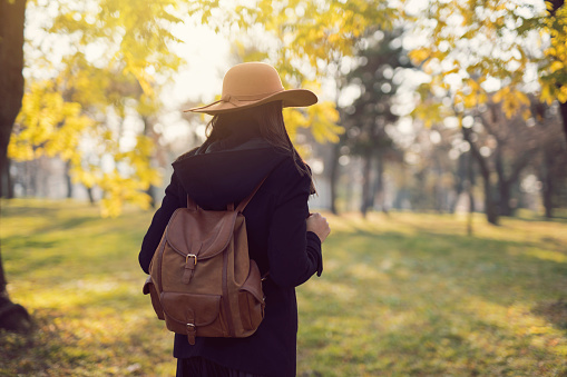 Rear view of an unrecognizable woman with a hat and backpack on her shoulders going on an adventure.