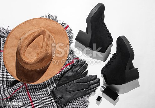 840310962istockphoto Autumn wardrobe. Women's things, shoes and accessories on a white background. Felt hat, suede shoes, leather gloves, a bottle of perfume. Flat lay 1153465046