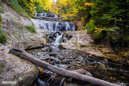 Beautiful Sable Falls surrounded by lush fall foliage cascades down a cliff on it's way to Lake Superior. Pictured Rocks National Lakeshore and the surrounding area of Munising are home to many of Michigan's Upper Peninsula waterfalls.