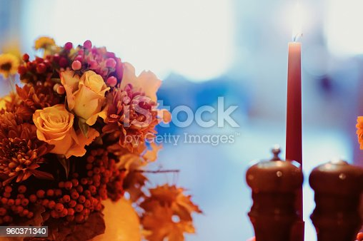 Autumn wedding decoration with flower composition with roses, chrysanthemum, maple leaves, pumpkin, books and candles. Haloween concept