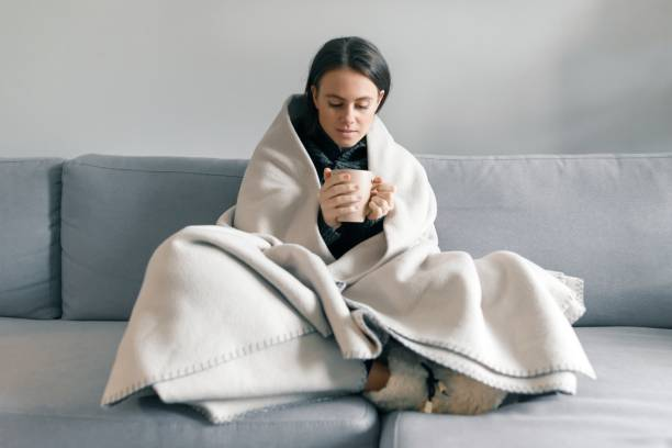 Autumn winter portrait of young girl resting at home on the sofa with cup of hot drink, under warm blanket Autumn winter portrait of young girl resting at home on the sofa with cup of hot drink, under warm blanket. wrapped in a blanket stock pictures, royalty-free photos & images