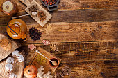 Autumn winter still life. Teapot with tea on a wooden table with honey ginger and rosehip. The apartment lay. The space under the text. Comfort