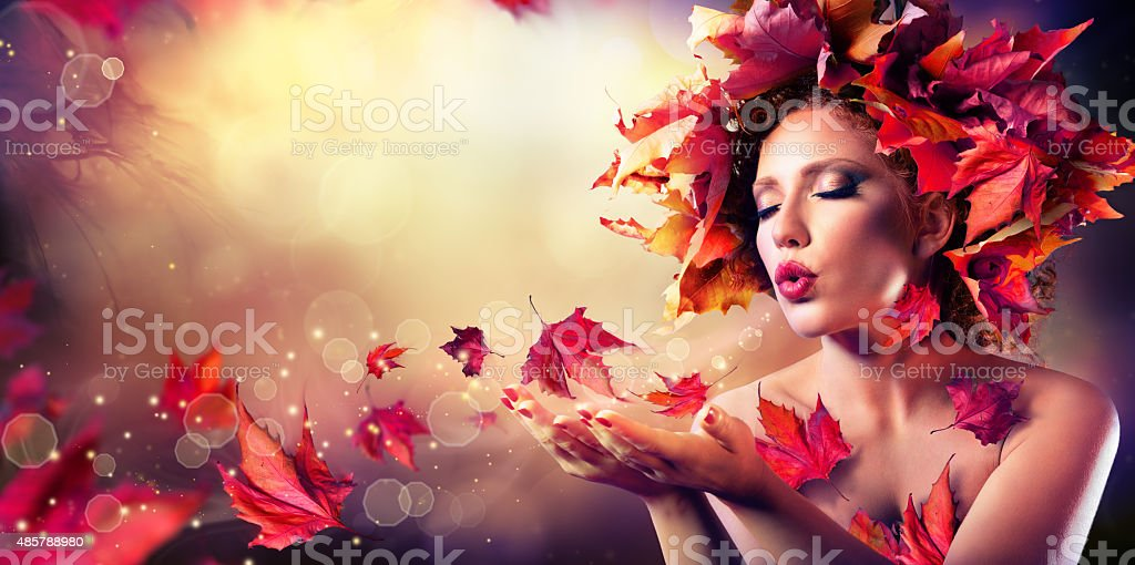 Autumn woman blowing red leaves in fairy scene stock photo
