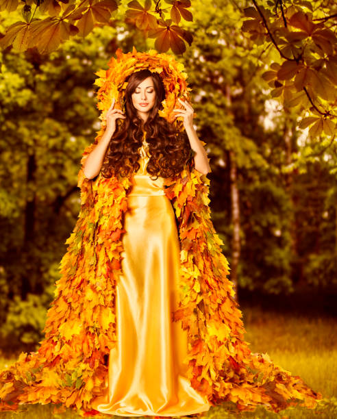 Autumn Woman, Fashion Model in Fall Forest, Girl in Autumnal Yellow Leaves Art Dress stock photo