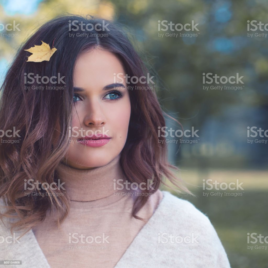 Autumn Woman Fashion Model with Fall Leaves in the Autumn Park Outdoors stock photo