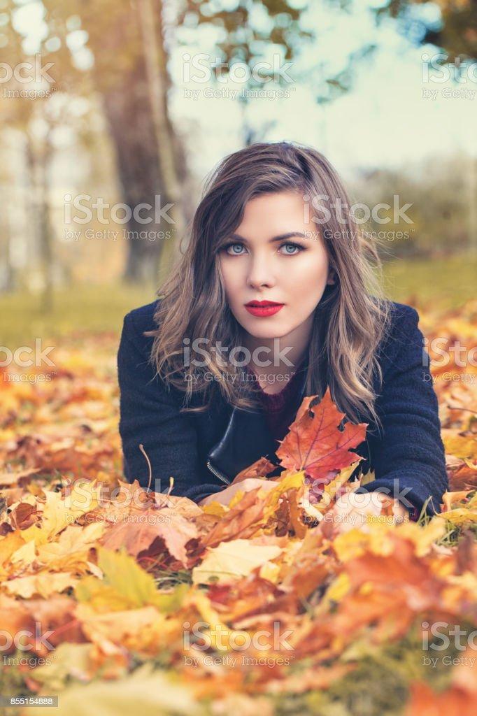 Autumn Woman Lying on Fall Leaves in Beautifu Autumn Park Outdoors stock photo
