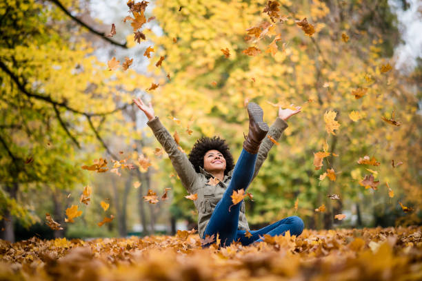 Autumn woman sitting with arms raised stock photo