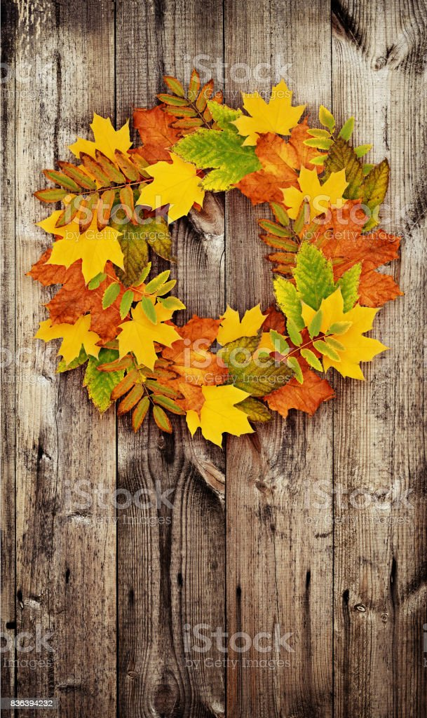 Autumn wreath from colored dry leaves on door stock photo
