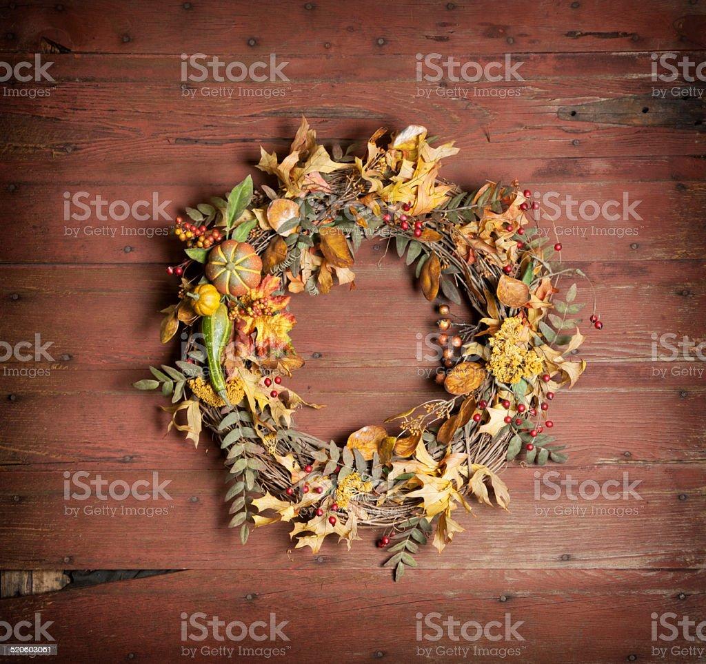 Autumn wreath of leaves on rustic wood door stock photo