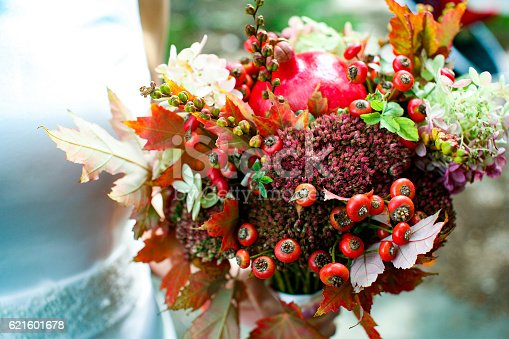 bride holding wedding bouquet of autumn leaves, flowers, berries and pomegranate. closeup