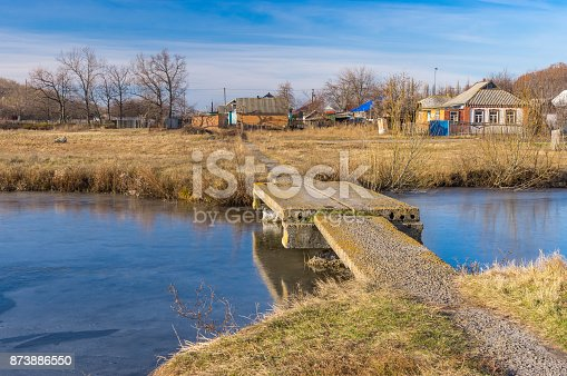 istock Autumnal landscape with small simple pedestrian bridge over Orchyk river in Karlovka town, Ukraine 873886550