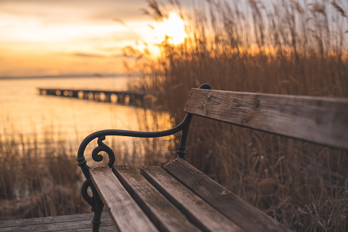 Autumnal sunset at the lake. Lakeshore with a bench and wooden walkway.