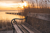 Autumnal sunset at the lake. Lakeshore with a bench and wooden walkway. In the background the footbridge, the reed and the setting sun. Autumn at the lake. Winter at the lake