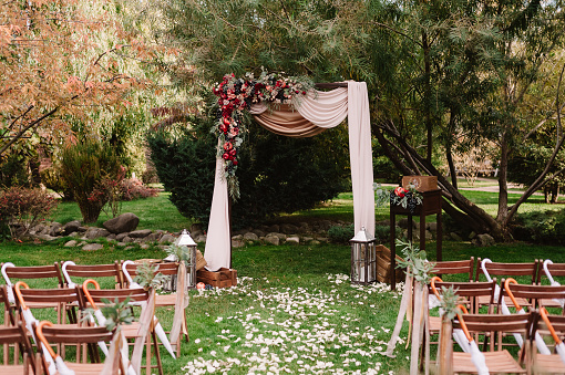Autumnal wedding archway decoration of roses, apples, grape and pomergranate, in red colour, closeup