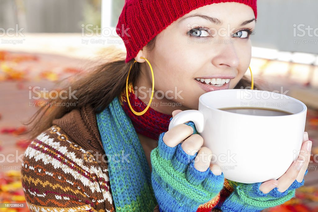Autumn-Smiling woman holding cup of coffee royalty-free stock photo
