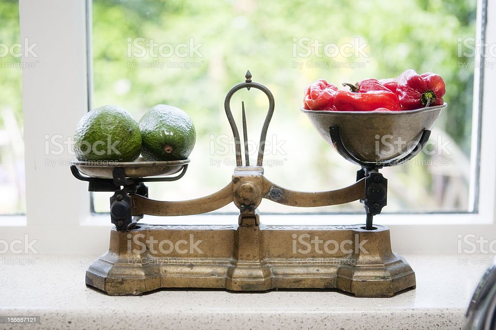 avacados and red peppers on an antique kitchen scales stock photo