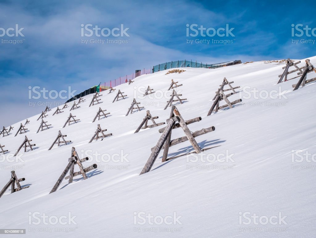 Avalanche barrier or protection made by wood in ski slope. stock photo
