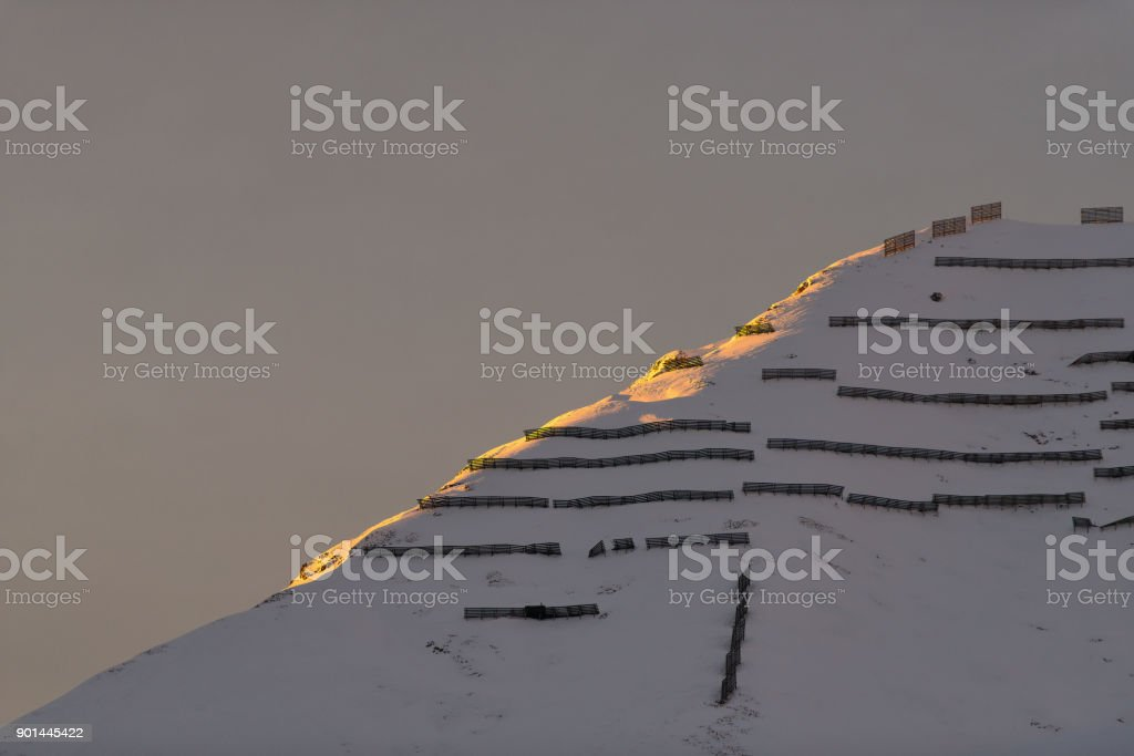 Avalanche barriers in the mountains at sunset stock photo